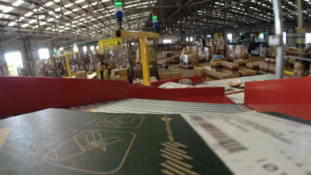 pov package moving along automated sorting machine - cardboard box stock videos & royalty-free footage