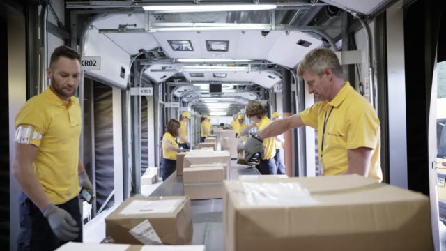 TIME-LAPSE POV Package travelling on the conveyor belt and postal workers are sorting them