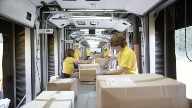 pov package travelling on the conveyor belt and the postal workers are sorting the surrounding packages - production line stock videos & royalty-free footage