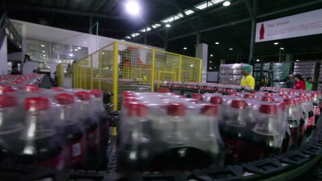Packaged bottles of Coca Cola soda move along the production line at the Coca Cola Co bottling plant in Hmawbi Packaged bottles of Coca Cola...