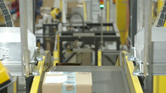 packages flow along a conveyor belt at an amazon packaging center on november 28, 2019 in brieselang, germany. amazon is anticipating a strong... - conveyor belt stock videos & royalty-free footage
