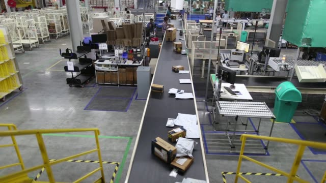 Packages move along a conveyor belt at the Amazoncom Inc fulfillment center in Hyderabad India on Thursday Sept 7 Employees move packages from a...