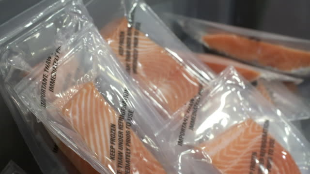 Packages of salmon fillets sealed in plastic and packed into carton at fish processing factory