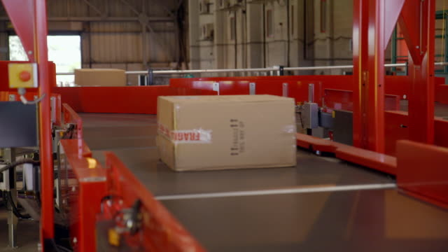 packages placed on automated sorting machine - box container stock videos & royalty-free footage