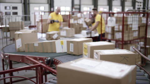 ld r/f packages travelling on the conveyor belt to the workers taking them off it and stacking them - post structure stock videos & royalty-free footage