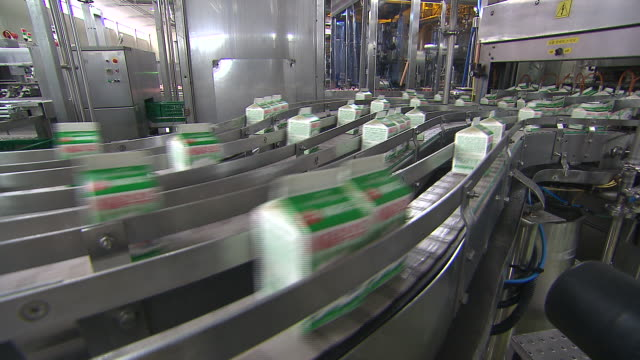 Packed milks moving on conveyor belt.