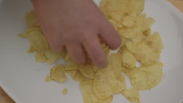 vídeos y material grabado en eventos de stock de a packet of crisps is poured onto a plate and then removed in clumps by a hand, uk. - patatas fritas de churrería