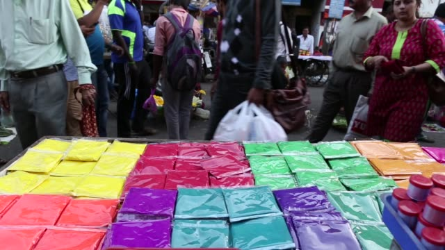 packets of colored powders sit on display at a roadside market stall ahead of holi celebrations in mumbai india on saturday march 11 shoppers walk... - body adornment stock videos and b-roll footage