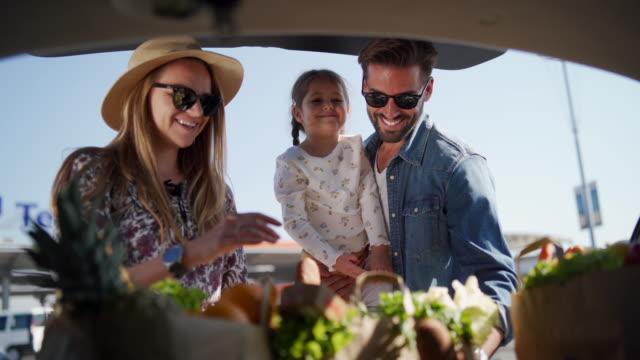 vídeos de stock, filmes e b-roll de mantimentos da embalagem no tronco de carro - família jovem