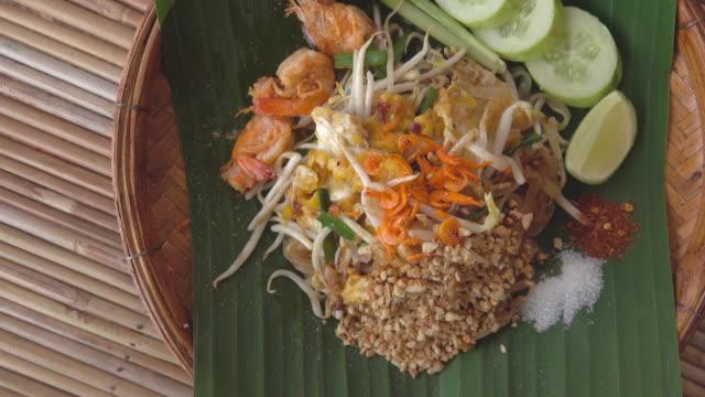 vídeos de stock e filmes b-roll de pad thai on bamboo plate top view - cultura da ásia oriental