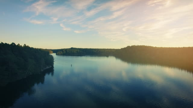 paddle boarding on a lake in sweden - pagaiare video stock e b–roll
