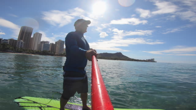 pov paddle of sup stand up paddleboarding surfing near diamond head state monument in waikiki, oahu, hawaii. - oar stock videos & royalty-free footage