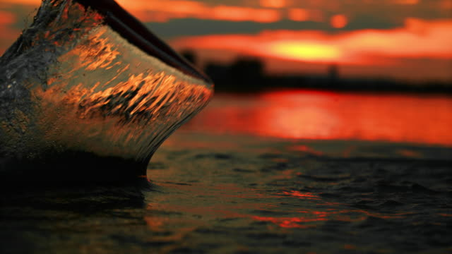 super slo mo paddle splashing water at sunset - using a paddle stock videos & royalty-free footage