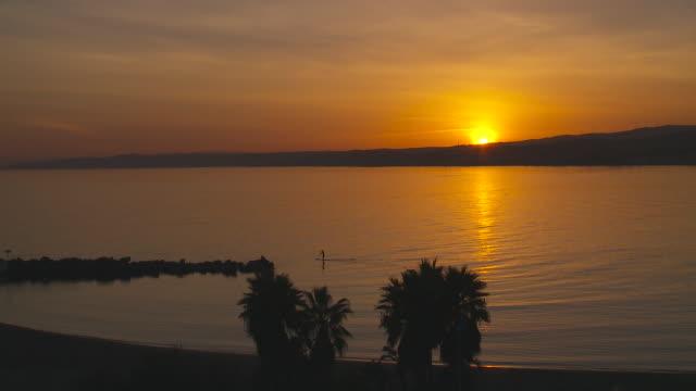 vídeos y material grabado en eventos de stock de paddle surfer negotiates cristo bay in soutern spain at sunset - anochecer
