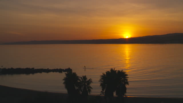 vídeos de stock e filmes b-roll de paddle surfer negotiates cristo bay in soutern spain at sunset - anoitecer