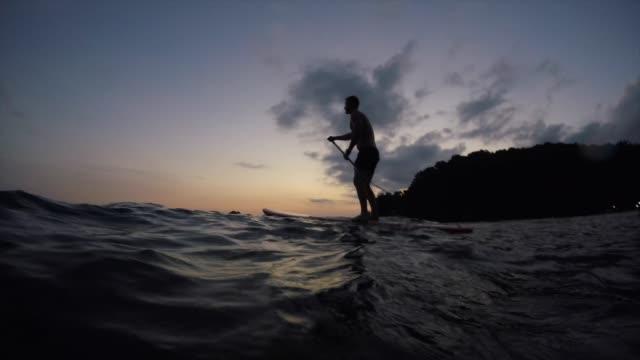 vídeos de stock, filmes e b-roll de paddleboarding na hora por do sol - verão