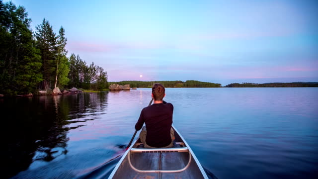 paddling a canoe on a lake in the wilderness pov - canoeing stock videos and b-roll footage