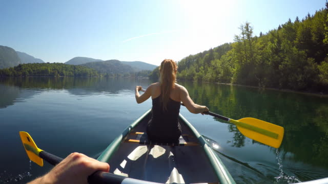 vídeos de stock e filmes b-roll de paddling canoe on a pristine lake - kayaking