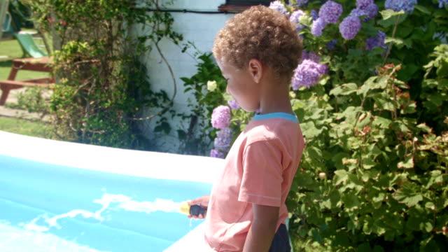 vidéos et rushes de hd: pataugeoire être remplie par sourire de petit garçon biracial - pataugeoire