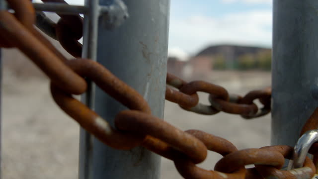 Padlock and chain on gate at empty industrial site - pan to lock