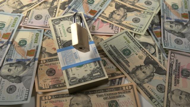 padlock falling on dollar bank notes, slow motion 4k - banconota da 10 dollari statunitensi video stock e b–roll