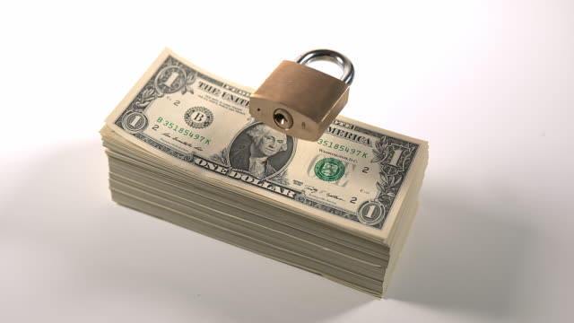 padlock falling on dollar bank notes, slow motion 4k - american one dollar bill stock videos & royalty-free footage
