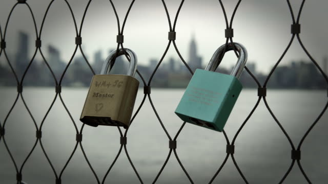 padlocks attached to fence along water in new york city. - durability stock videos & royalty-free footage