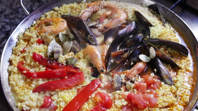 vídeos de stock e filmes b-roll de paella cooking in a pan - espanha