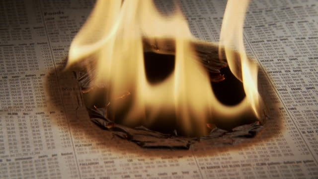 cu page of stocks being engulfed by flames - recession stock videos & royalty-free footage