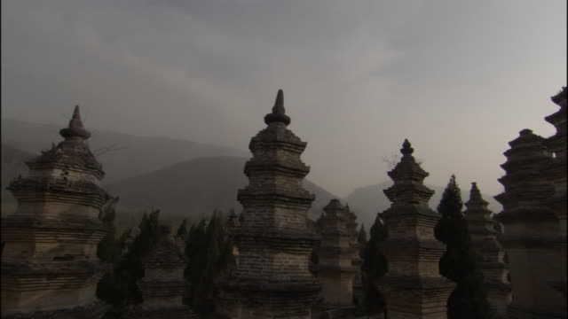 ms pan pagoda sculptures and dark sky at shaolin temple/ pan back across sculptures/ henan province, china - pagoda点の映像素材/bロール