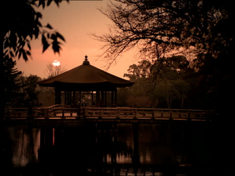 a pagoda-like gazebo rests on a bridge over a lake at golden-hour in japan. - gazebo stock videos and b-roll footage