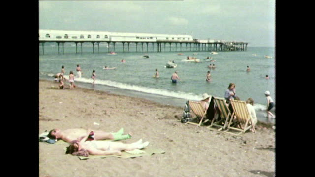 paignton beach and pier in devon, uk; 1981 - clear sky stock videos & royalty-free footage