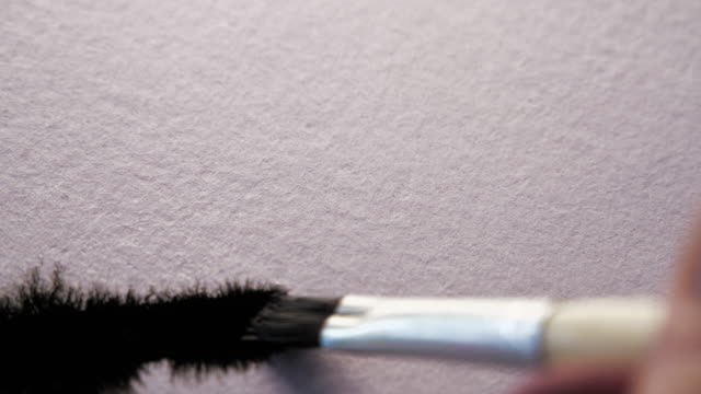 Paint brush painting black ink on white textured paper. Macro shot with amazing ink bleeds