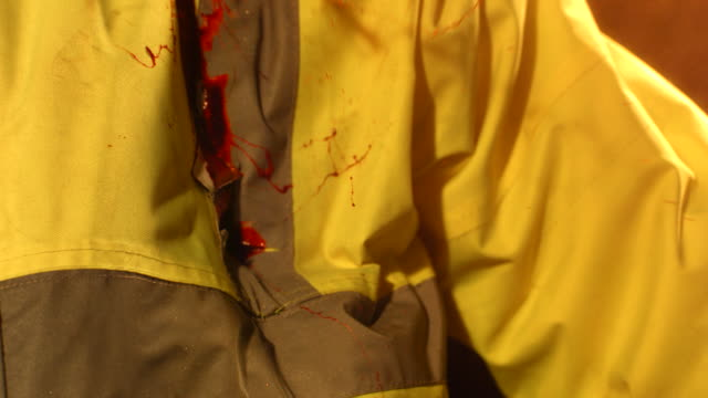 CU SLO MO Paintball hitting green jacket ( look like blood exiting from wound after shooting ) / Manchester, United Kingdom
