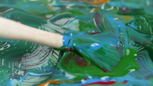 vidéos et rushes de paintbrush mixes various acrylic paints together - pinceau