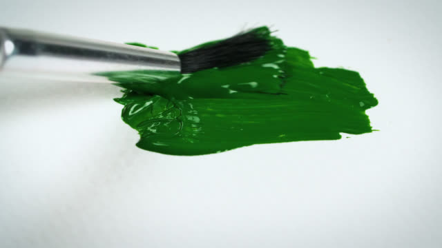 paintbrush paints green paint onto white paper - acrylic painting stock videos & royalty-free footage