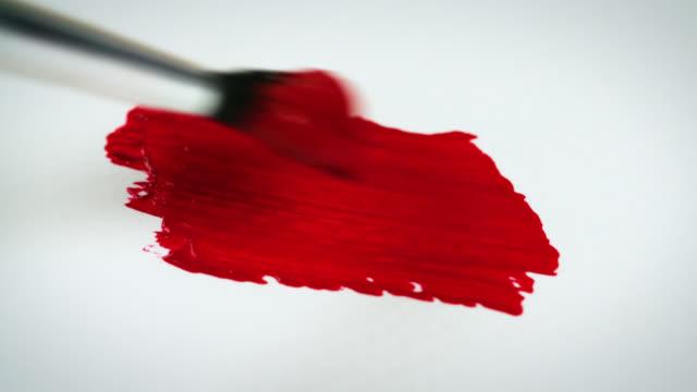 stockvideo's en b-roll-footage met paintbrush paints red paint onto white paper - verfkwast