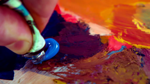 paintbrush with oil paint on a classical palette - oil paint stock videos and b-roll footage