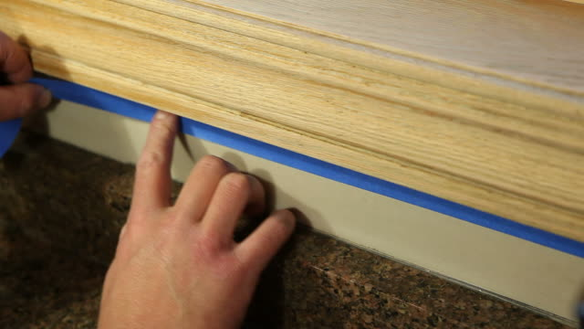 painter applying blue masking tape to protect area - house painter stock videos and b-roll footage