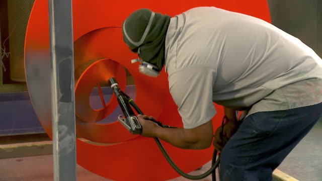 ms zi painter covers art piece metal sculpture with orange colored powder coat / cathedral city, california, usa  - one mid adult man only stock videos & royalty-free footage