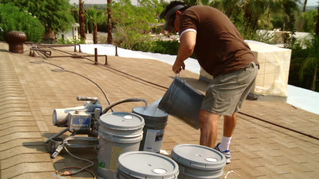 ms zi painter on roof pours hyper glass paint into bucket as other worker in background / rancho mirage, california, usa.   - rancho mirage stock videos & royalty-free footage