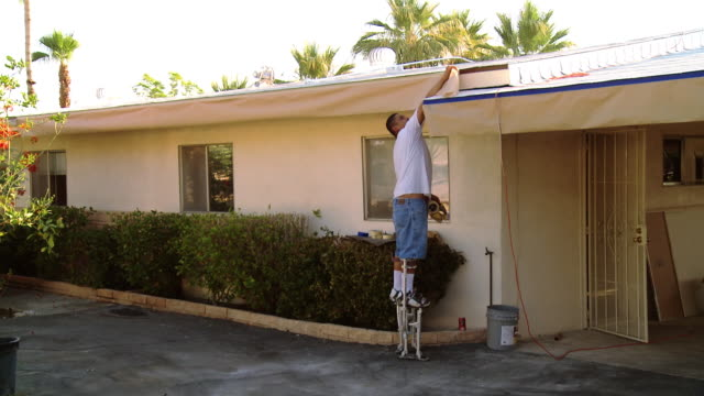 ws painter on stilts walking alongside eaves of residential home / rancho mirage, california, usa.  - eaves stock videos and b-roll footage