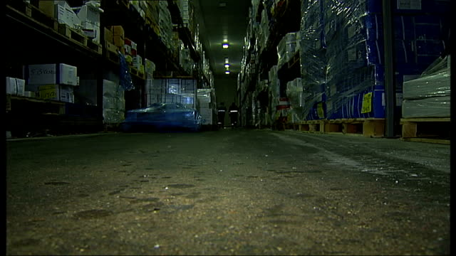 stockvideo's en b-roll-footage met painter practices in billingsgate freezer for south pole trip england london billingsgate market int two men walk through concrete corridor into... - steurgarnaal