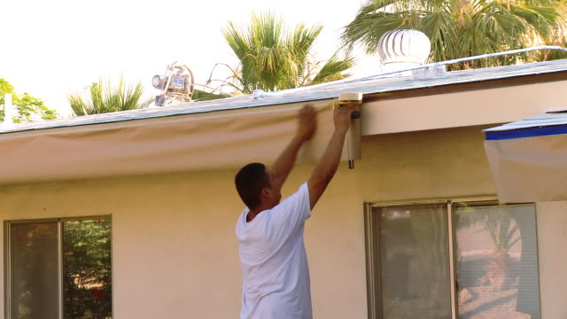 ms painter tapes masking paper to fascia of roof / rancho mirage, california, usa.  - rancho mirage stock videos & royalty-free footage