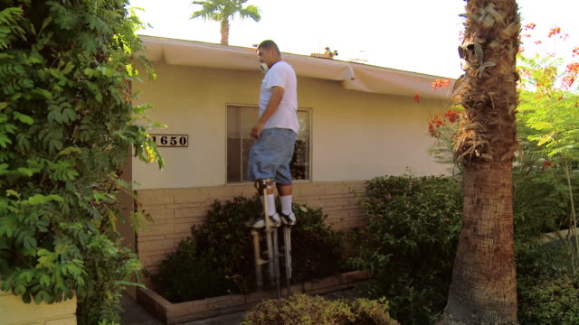 ws painter tapes masking paper to fascia of roof / rancho mirage, california, usa.  - stilts stock videos and b-roll footage