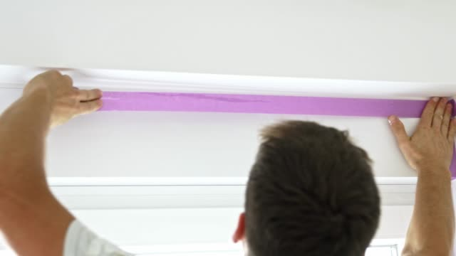 vídeos de stock e filmes b-roll de painter taping the window with painters tape - eslovénia