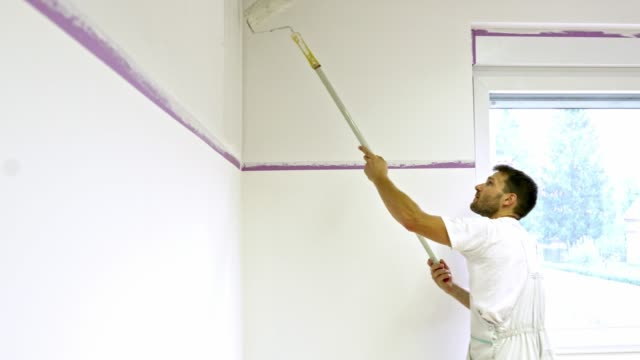 painter using a painting roller on extended handle to paint the wall - decorating stock videos & royalty-free footage