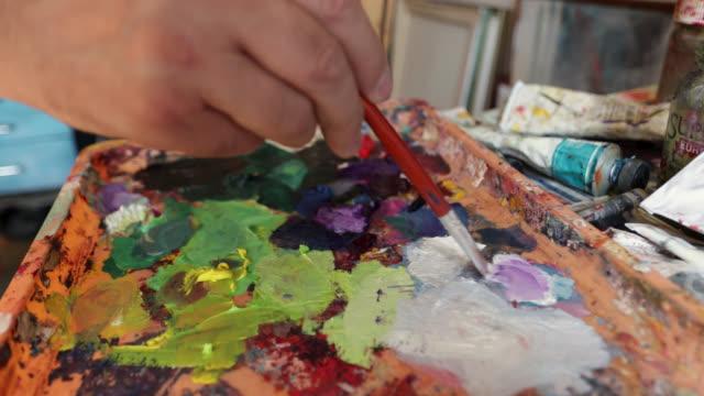 pittore che usa la sua tavolozza di colori e disegna in home studio - pittore video stock e b–roll