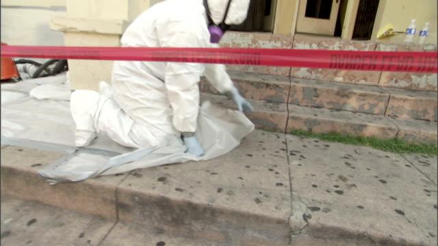 vídeos de stock e filmes b-roll de a painter wearing protective clothing removes a plastic drop cloth from a sidewalk. - pano de protecção