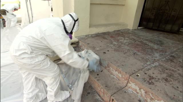 vídeos de stock e filmes b-roll de a painter wearing protective clothing rolls up a plastic drop cloth. - pano de protecção
